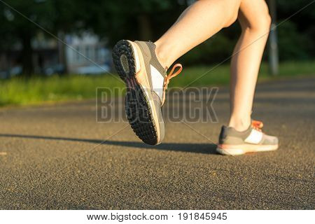 Runner With Running Shoes On Tarmac From The Side