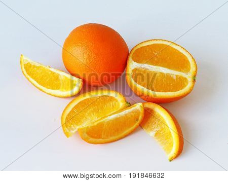 Cut and whole oranges on the table.