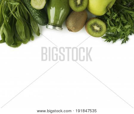 Green smoothie with apples parsley spinach cucumber and kiwi on a white background. Top view. Spinach smoothie and vegetables at border of image with copy space for text. Green fruit and vegetable on white background.