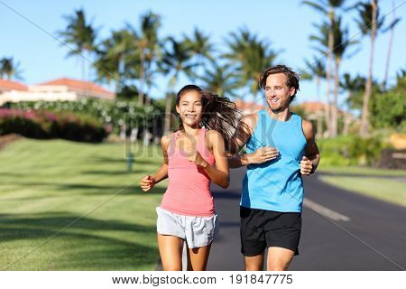 Happy runners couple having fun running training together in summer outdoors. Asian woman with personal trainer motivating for weight loss program. Healthy lifestyle
