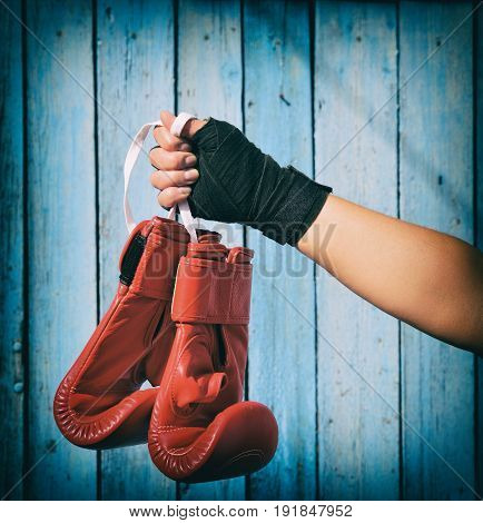 Female hand holds a pair of red kickboxing gloves on a blue wooden background