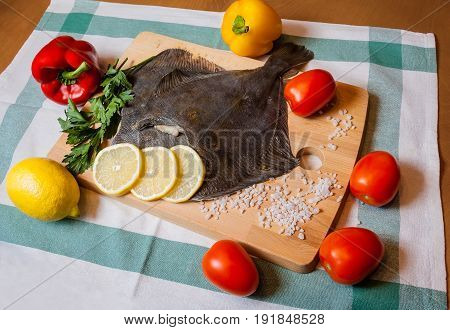 Fresh raw flounder with vegetables on cutting board
