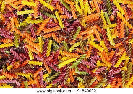 Multicolored fusilli raw pasta suitable as food background.