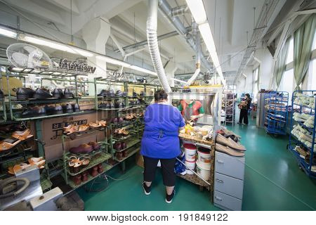 MOSCOW - FEB 21, 2017: Women glue shoes in workshop in Ralf Ringer factory. company production is 1,5 million pairs per year