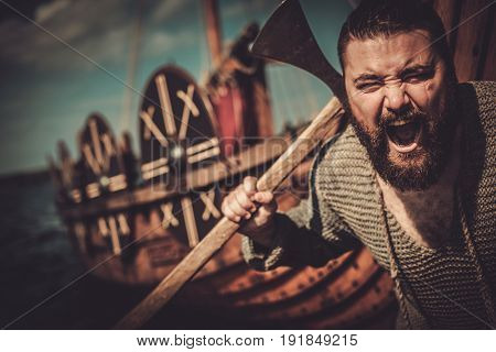 Viking with axe standing near drakkar on the seashore.