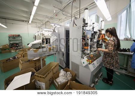 MOSCOW - FEB 21, 2017: Woman works on machine in workshop in Ralf Ringer factory. Company production is 1,5 million pairs per year
