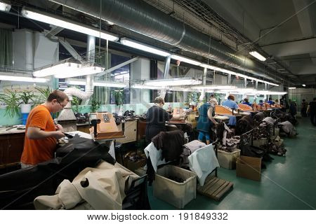MOSCOW - FEB 21, 2017: People work in workshop with leather and suede cutting machines in Ralf Ringer factory. Company production is 1,5 million pairs per year