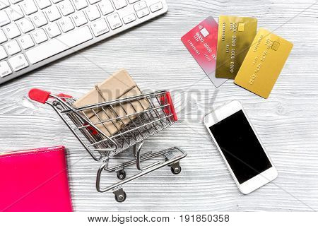 trolley, keyboard, mobile and credit cards for online purchasing on gray desk background top view mockup