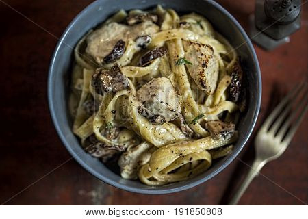 Tagiatelle pasta with mushrooms chicken parmesan on brown table