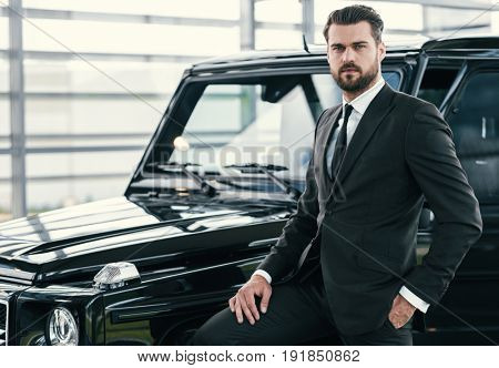 Well-dressed customer choosing new premium car at a dealership showroom
