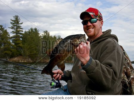 bass fisherman in a boat holding a smallmouth bass with a freshwater lake in the background poster