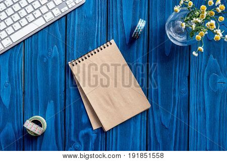 home office set with flowers, keyboard and notebook on bright blue desk background top view mock-up