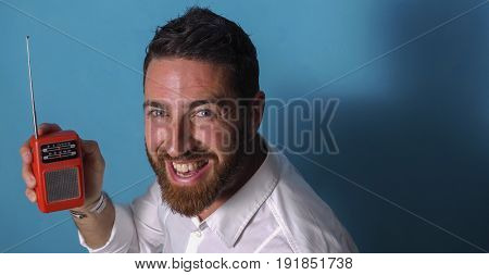 Portrait of a happy and cheerful man who hears a small transistor on a blue background