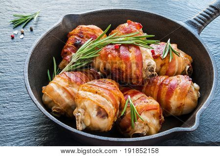 Bacon wrapped chicken drumsticks in a black cast-iron skillet on the stone background.