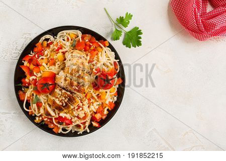Grilled chicken breast and pasta with tomatoes red bell peppers and parsley on the black plate top view.