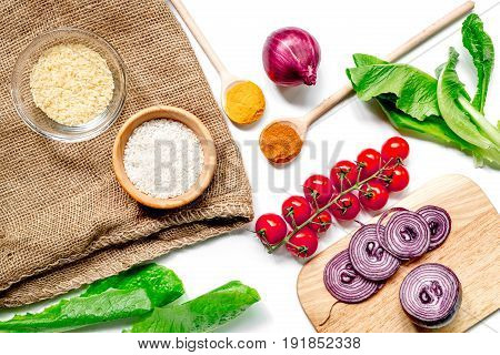 rice, spices and vegetables for paella on white kitchen desk background top view