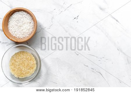 cooking paella with vegetables and rice ingredients on white kitchen desk background top view mockup