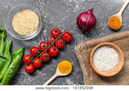 rice, spices and vegetables for paella on dark kitchen desk background top view