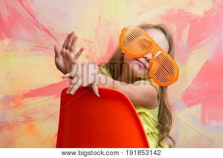 Happy Child Sitting On Orange Chair In Summer Glasses