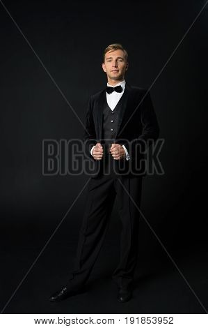 formal serious fashionable handsome man in black tuxedo suit and bow tie on black background