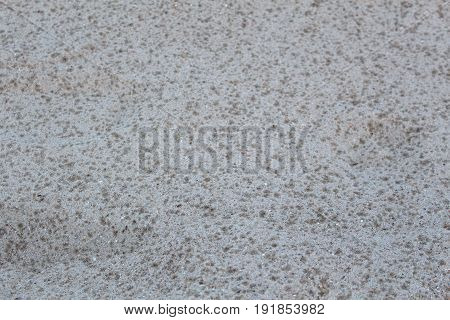 Small sand stone of sand wall texture. Natural grey sand stone for design with copy space for text or image. background of sand with raindrops.
