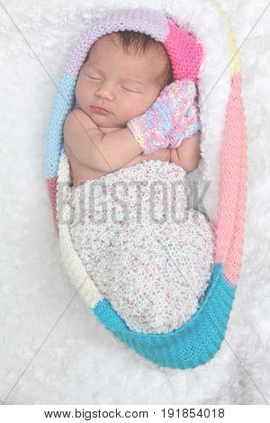 newborn baby girl bundled up in a rainbow colored snuggle sack. She is lying and sleeping  on a white bouncle blanket.  concept of new life
