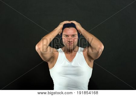 Serious Man With Muscular Hands In White Vest And Hat