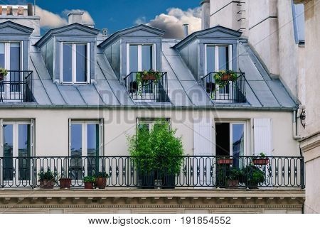 Part of the house in Paris with attic rooms on the roof and a balcony decorated with greenery and flowers.