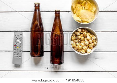 home party with TV watching, snacks, pop corn, chips and beer on white background top view