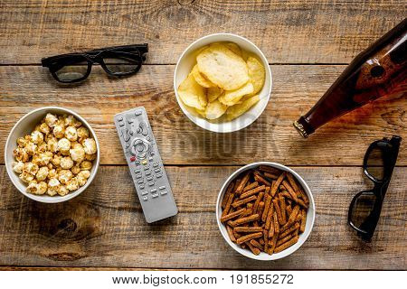 cinema and TV whatching with beer, crumbs, chips and pop corn on wooden background top view