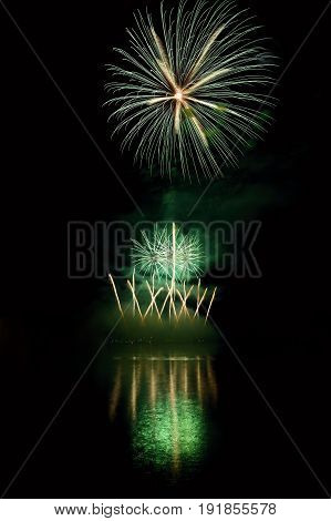 Beautiful Colorful Fireworks On The Water Surface With A Clean Black Background. Fun Festival And In