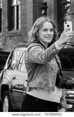 New York City United States - April 23 2017: A woman tourist taking a selfie of the Brooklyn Bridge