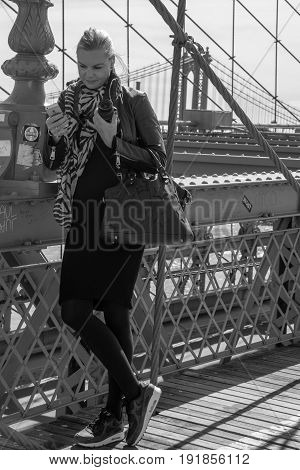 New York City United States - April 23 2017: A woman tourist looking at her cellphone at Brooklyn bridge