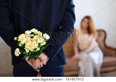 Valentine's Day Or Anniversary Concept - Man Hiding Flowers Behind His Back