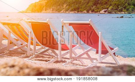 Appealing Beach Chairs on Sand. Palm Trees and Ocean in Background. Haad Salat. Ko Phangan, Thailand.