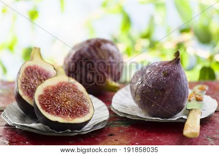 Fresh figs cut on pewter plates outdoors