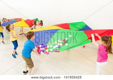 Group of children waving their arms causing the balls to pop up and off of the parachute
