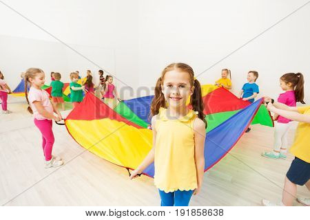 Portrait of six years old girl holding the parachute handle and playing with her friends in gym