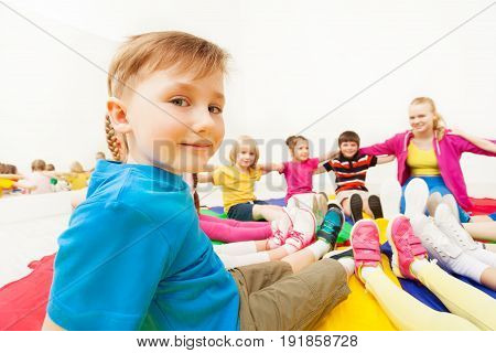 Close-up portrait of blond preschool boy playing circle games with friends, sitting in on the floor in gym