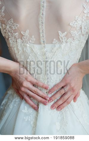 Lace white wedding dress with long sleeves. Womans hands.
