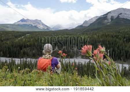 Picture of a woman at a viewpoint looking at Threepoint mountain in Kananaskis, Alberta,Canada.