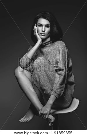 beautiful girl in oversize grey sweater sitting on bar stool. studio portrait on dark background. copy  space. monochrome
