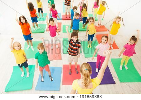 Group of age-diverse kids in sportswear standing on mats with arms upwards during gymnastic lesson in gym