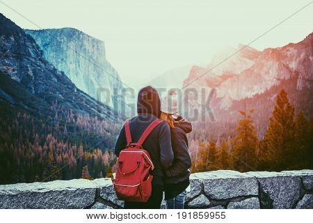 Romantic view of a young couple enjoying famous Tunnel View in beautiful golden morning light at sunrise in Yosemite Valley in summer with retro vintage Instagram style filter effect California USA