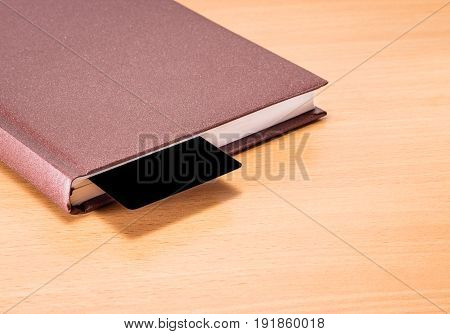 A solid diary with a black bookmark on a wooden background a place for writing