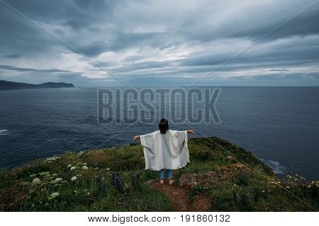Young yoga practicing woman is finding peace with her inner self and nature while meditating on edge of cliff overlooking stormy ocean and mountains