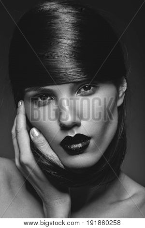 beautiful young woman with black lips and shiny healthy hair. beauty shot on black background. copy space.