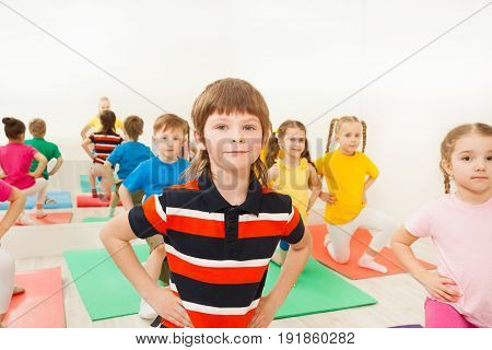 Portrait of Caucasian six years old boy doing kneeling exercises during gymnastic group session in gym