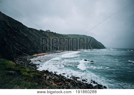 Cloudy and foggy shot of rocky stormy beach with huge waves crushing on cliffs and rocks with few surfers riding in hazardous conditions