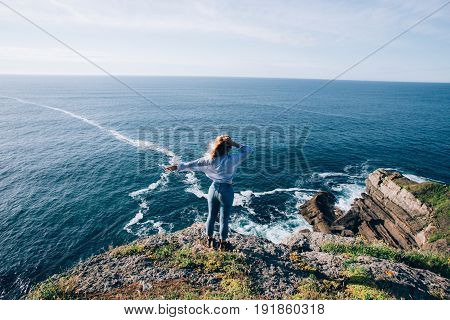 Blonde pretty woman in jeans and shirt looks at amazing ocean scenery waves and cliffs wind plays with her hair and she dreams about future and peace